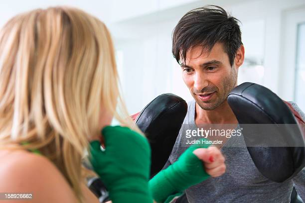 Boxer practicing with trainer in gym