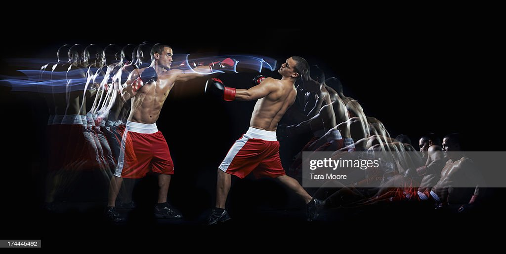 boxer punching other boxer with multiple strobe : Stock Photo