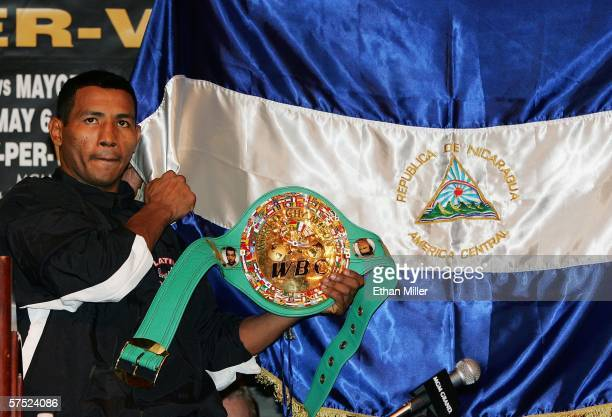 Boxer Ricardo Mayorga of Nicaragua holds up his WBC super welterweight championship belt in front of a Nicaraguan flag during a news conference at...