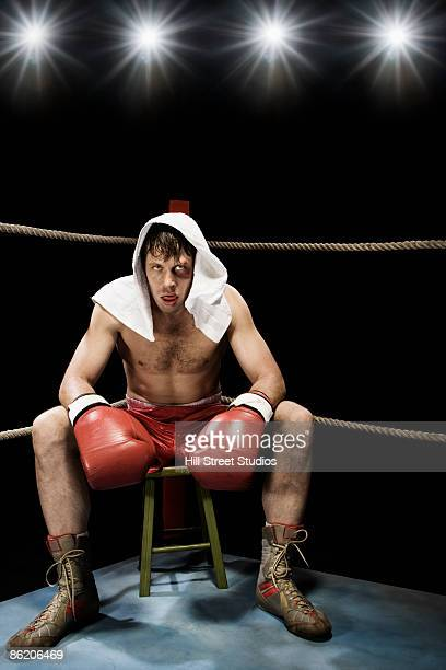 Boxer sitting on stool in corner of boxing ring