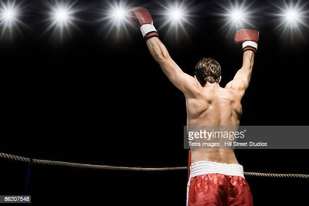 Boxer standing in boxing ring with gloves raised