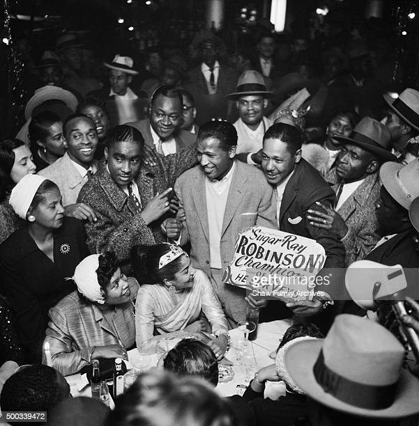 Boxer Sugar Ray Robinson is surrounded by a crowd in 1955