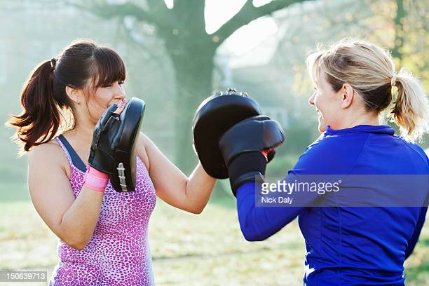 Boxer training with coach outdoors