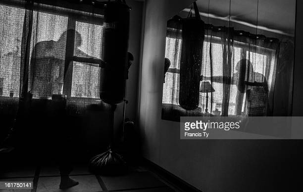 Boxer trains on a heavy bag in front of a mirror at a home gym.
