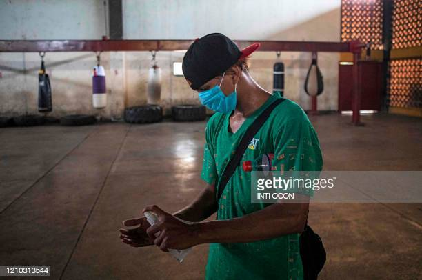 """Boxer wears a face mask and sprays alcohol in his hands after a training session at """"Roberto Huembes"""" boxing gym in Managua on April 14, 2020. -..."""