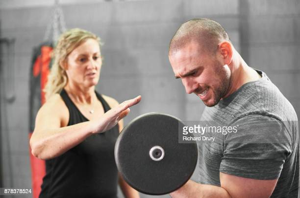 Boxer weightlifting with personal trainer