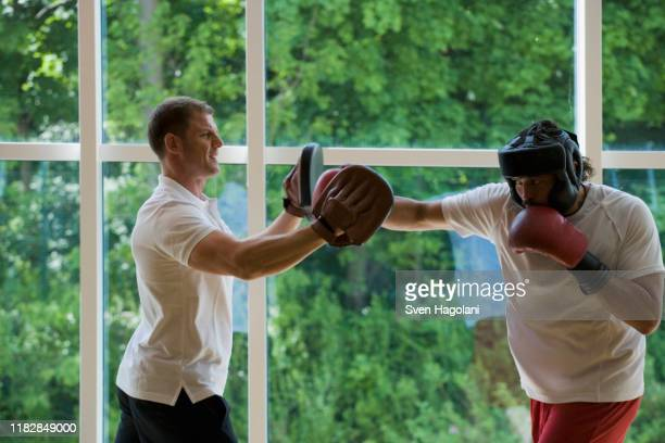 a boxer working with a trainer - boxing shorts stock pictures, royalty-free photos & images