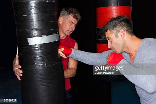 Boxer working with trainer in gym