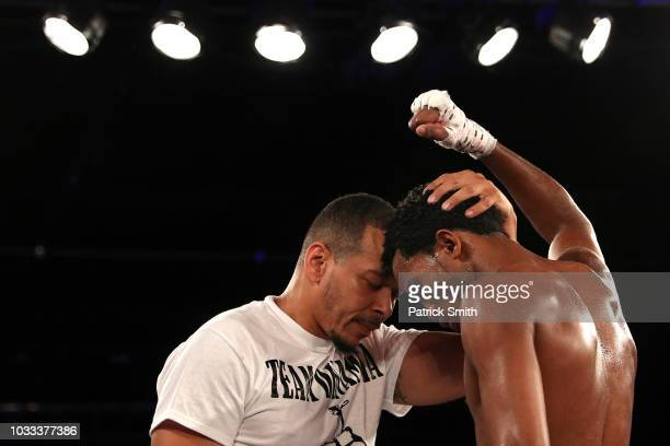Boxer Yueri Andujar shares a moment with his trainer Sensei Guerrido after defeating Crystian Peguero in his pro boxing featherweight debut bout at...