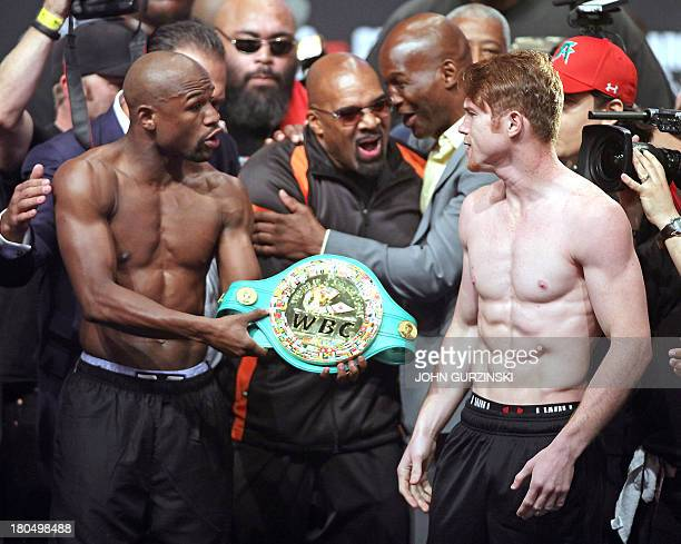 Boxers Floyd Mayweather Jr of the US offers Canelo Alvarez of Mexico his championship belt during the official weighin for their bout at the MGM...