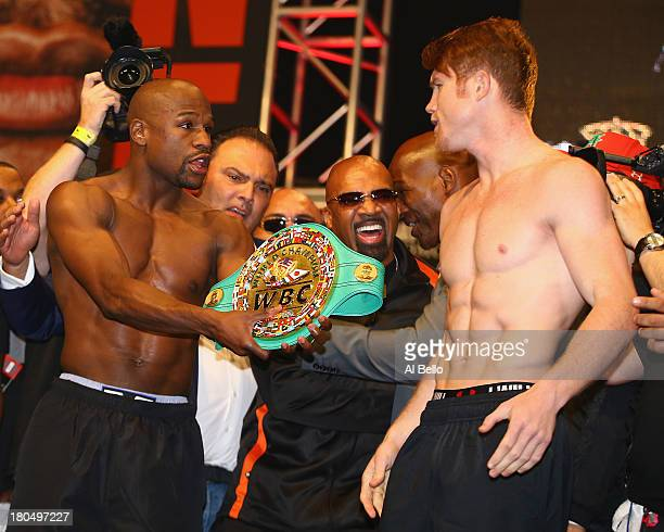 Boxers Floyd Mayweather Jr offers Canelo Alvarez his championship belt during the official weighin for their bout at the MGM Grand Garden Arena on...