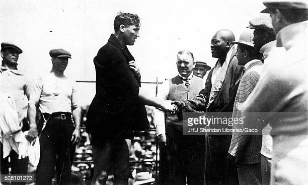 Boxers Jack Johnson and Jess Willard surrounded by other industry members shake hands before their famous fight in the 26th round of the world...