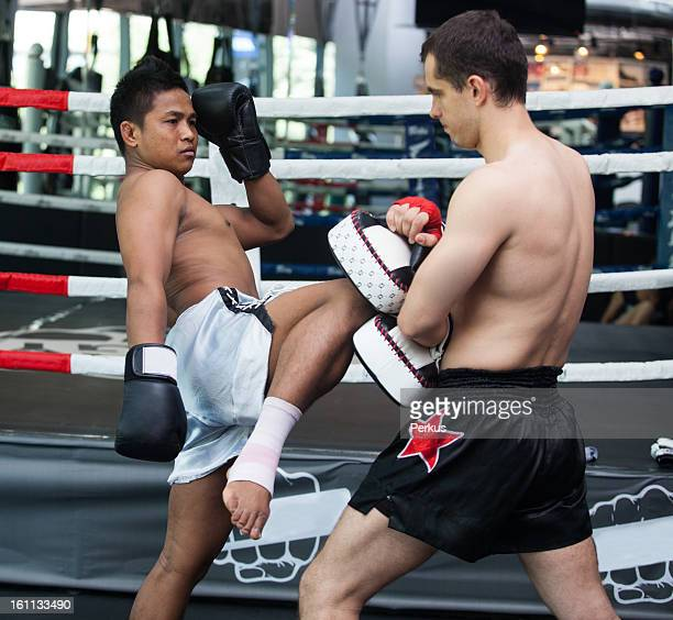 Boxers practicing Thai boxing in the boxing ring