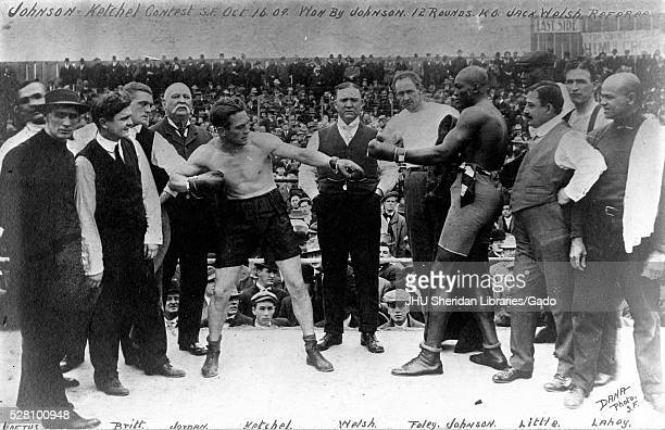 Boxers Stanley Ketchel and Jack Johnson stand in the ring before their famous match with California boxing referee Jack Welsh standing between the...