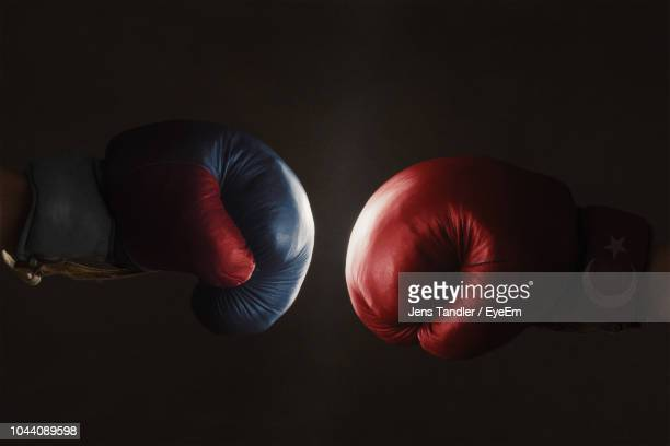 boxers wearing boxing gloves touching over black background - boxing gloves stock pictures, royalty-free photos & images