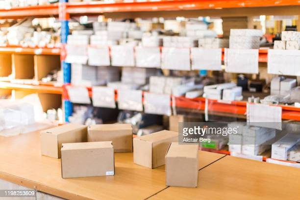 boxes awaiting delivery in distribution area of small business - post structure stock pictures, royalty-free photos & images