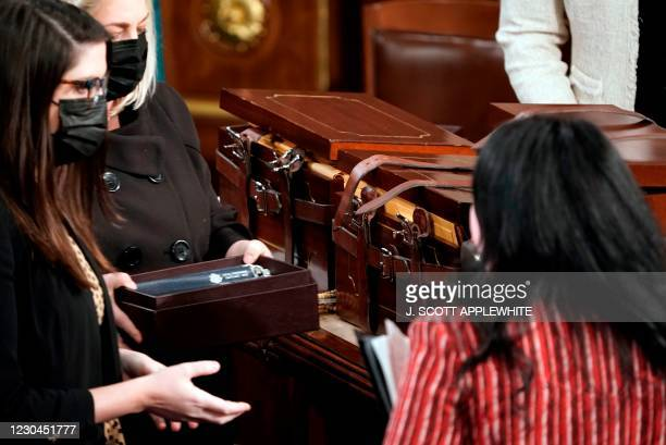 Boxes containing state Electoral College votes are opened as a joint session of the House and Senate convenes to confirm the Electoral College votes...