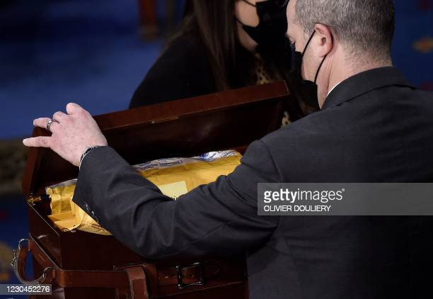 Boxes containing state Electoral College votes are opened during a joint session of Congress at the US Capitol on January 6, 2021 in Washington, DC....