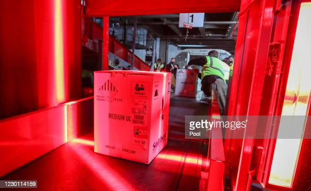 Boxes containing the first shipments of the Pfizer and BioNTech COVID-19 vaccine are unloaded from air shipping containers and scanned at UPS...