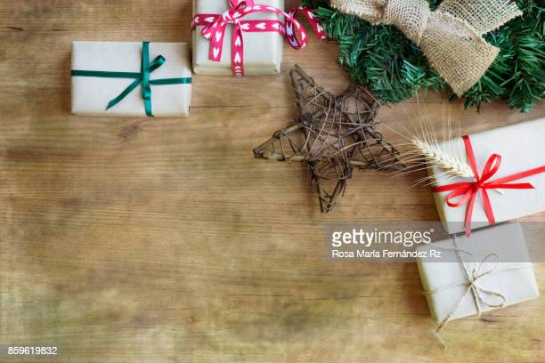 Boxes gifts wrapped in rustic paper and colored ribbons on wood background. High angle view and copy space.