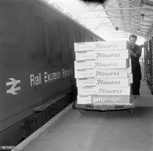 Boxes of flowers being wheeled along a platform Flowers could be moved around the country quickly by rail and the containers they were transported in...