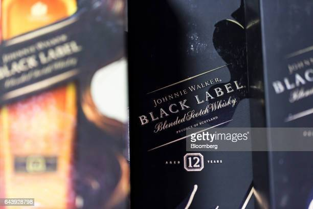 Boxes of Johnnie Walker Black Label whiskey produced by United Spirits Ltd a distiller partly owned by Diageo Plc sit on display at a roadside liquor...