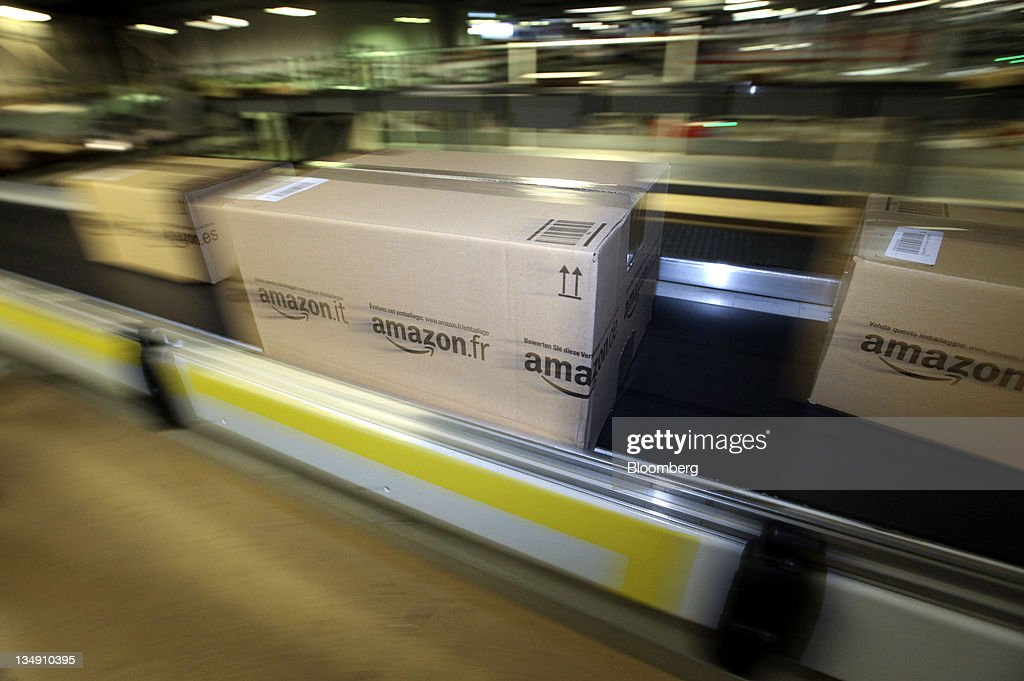 Boxes of merchandise move along the conveyor belt at the Amazon.co.uk. Marston Gate 'Fulfillment Center,' the U.K. site of Amazon. com Inc., in Ridgmont, U.K., on Monday, Dec. 5, 2011. Amazon.com Inc.'s share of the tablet computer market will surge to 14 percent this quarter as consumer demand catapults the Kindle Fire to the No. 2 spot after Apple Inc.'s iPad, according to research firm IHS Inc. Photographer: Chris Ratcliffe/Bloomberg via Getty Images