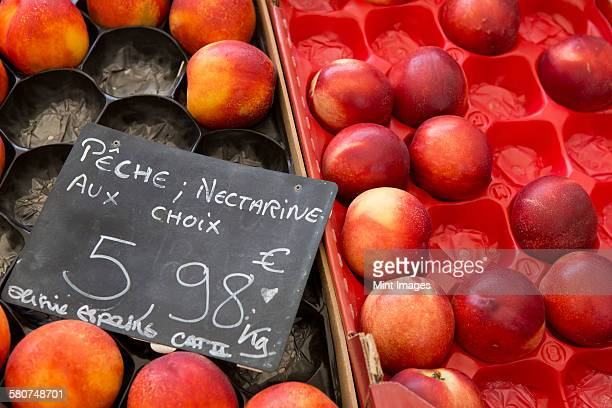 Boxes of nectarines on a fruit stall with a price label.