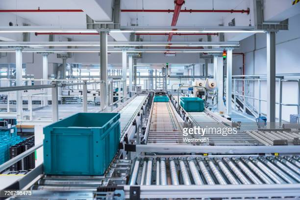 Boxes on conveyor belt in modern automatized high rack warehouse