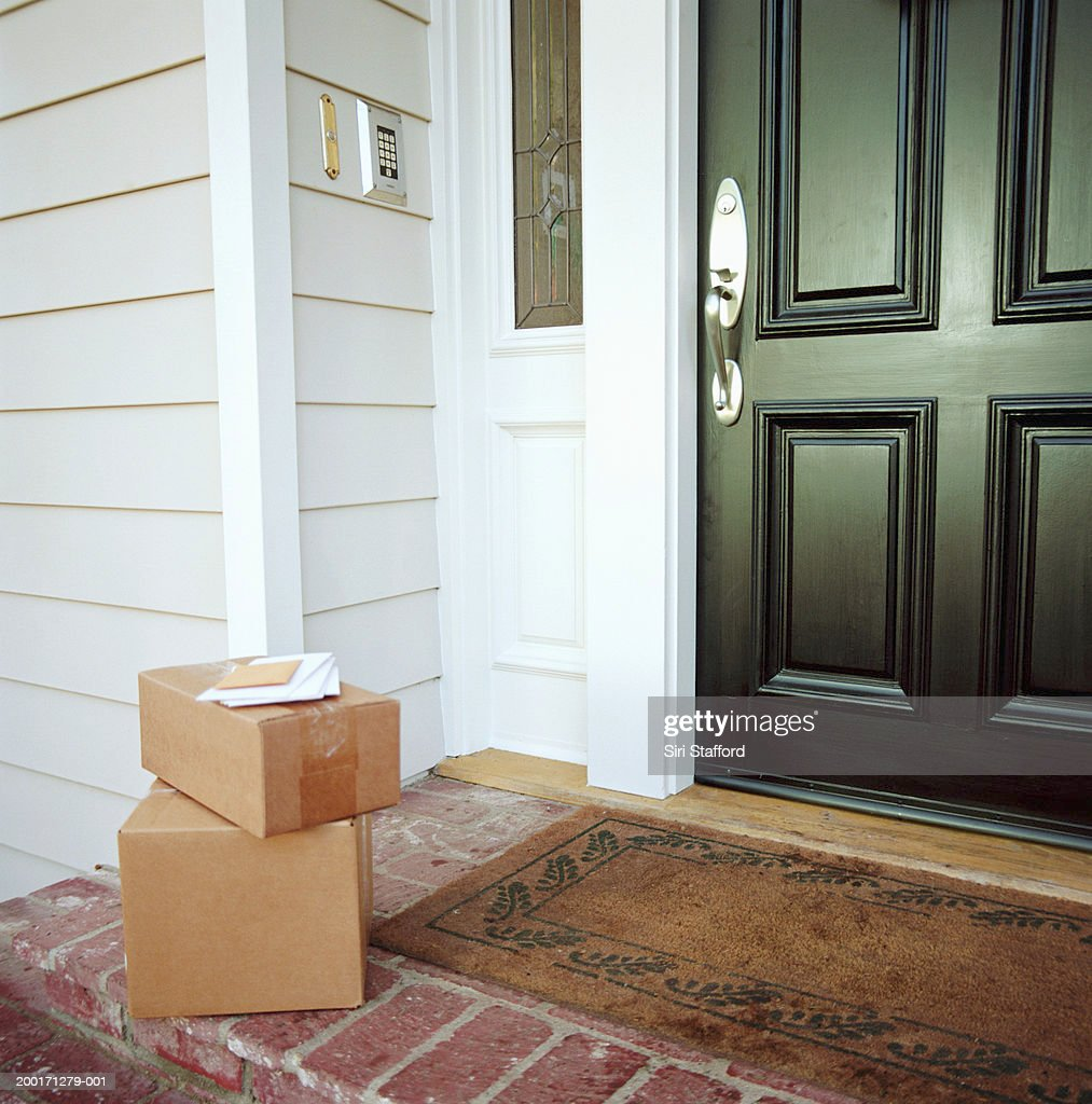 Boxes on doorstep of house : Stock Photo