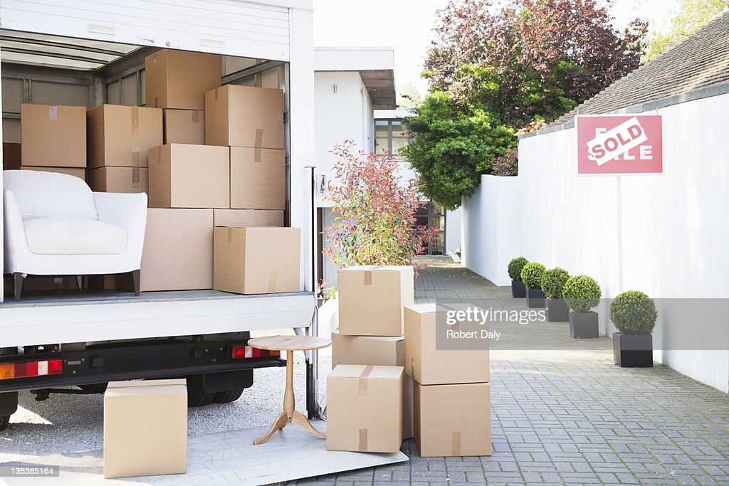 Boxes on ground near moving van : Stock Photo