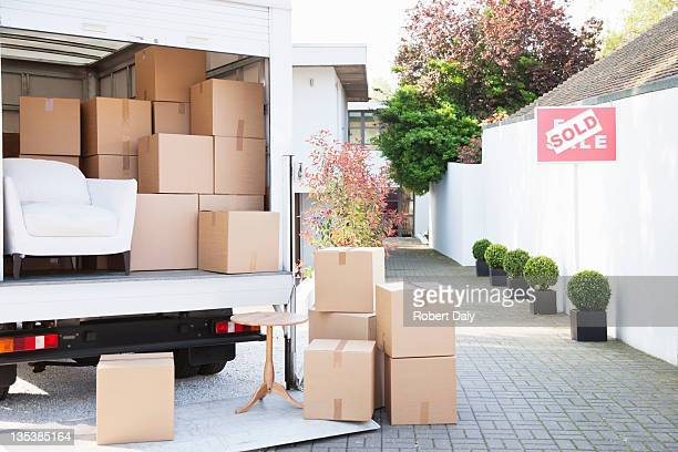 boxes on ground near moving van - unpacking stock pictures, royalty-free photos & images