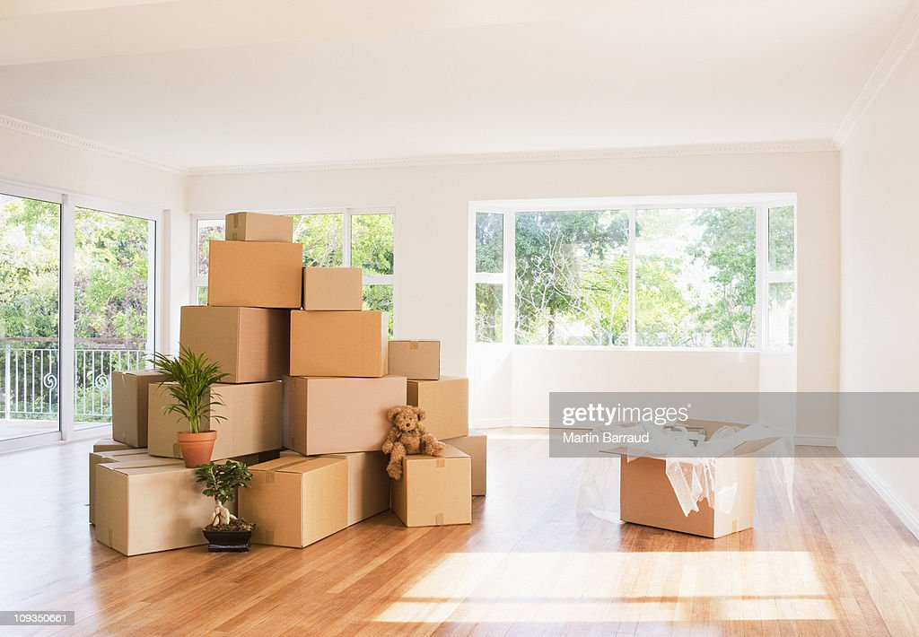 Boxes stacked in living room of new house : Stock Photo