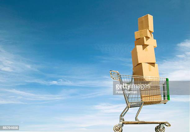 Boxes stacked in shopping cart.