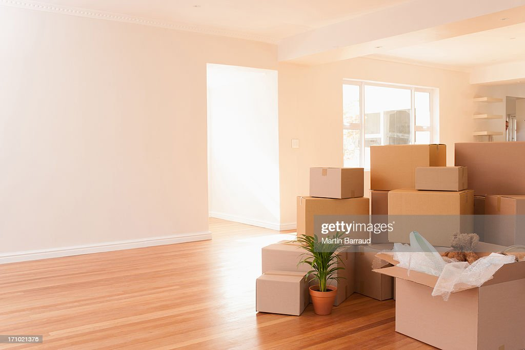 Boxes stacked on wooden floor of new house : Stock Photo