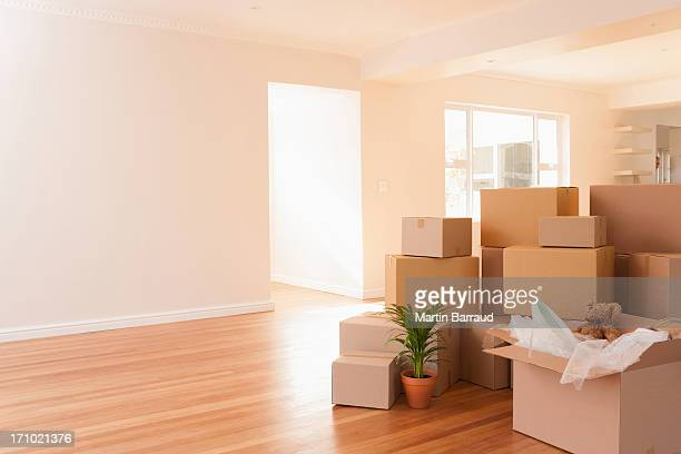 boxes stacked on wooden floor of new house - unpacking stock pictures, royalty-free photos & images