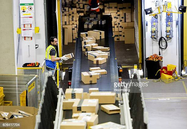 Boxes travel on a conveyor towards a shipping container at an Amazoncom Inc fulfillment center in Koblenz Germany on Tuesday Nov 29 2016 Ecommerce...