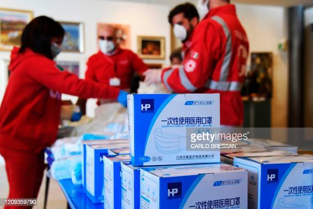 Boxes with protective masks sit in foreground as volunteers of the Italian Red Cross prepare protective masks which will be distribute for free to...
