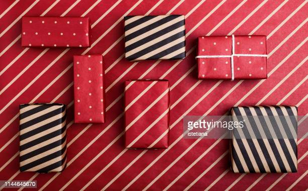 boxes wrapped in polka dot and striped paper on red craft paper - 包装紙 ストックフォトと画像