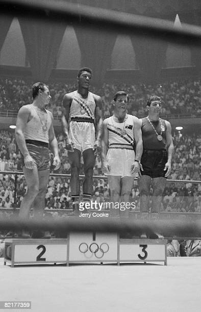 1960 Summer Olympics USA Cassius Clay victorious on stand with Poland Zbigniew Pietrzykowski Australia Anthony Madigan and Italy Guilio Saraudi after...