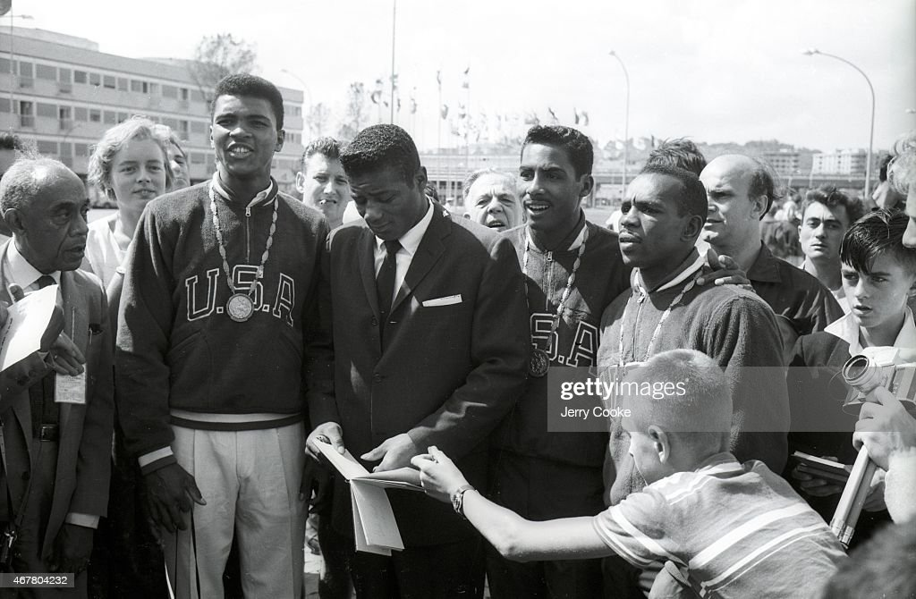 USA Cassius Clay (L) victorious with gold medal, standing with Floyd Patterson (C) surrounded by other athletes and fans. Jerry Cooke X6933 TK11 R7 F18 )