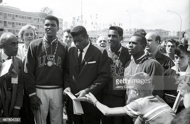 Summer Olympics: USA Cassius Clay victorious with gold medal, standing with Floyd Patterson surrounded by other athletes and fans. Rome, Italy...