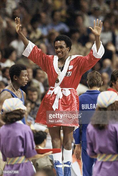 1976 Summer Olympics USA Sugar Ray Leonard victorious with gold medal on stand after winning Light Welterweight Final vs Cuba Andres Aldama at...