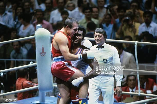 1980 Summer Olympics Cuba Teofilo Stevenson victorious holding Soviet Union Piotr Zaev after winning Heavyweight Final at Olympiski Sports Complex...