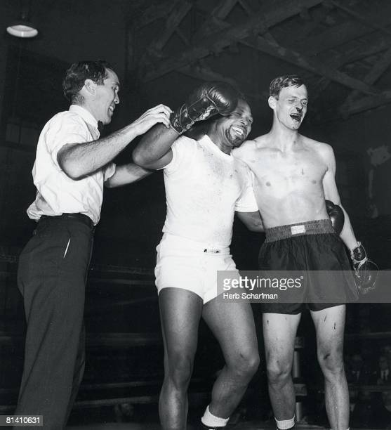 Boxing Archie Moore victorious with referee and SI writer George Plimpton after exhibiton fight at Stillman's Gym Plimpton sustaining bloody nose...