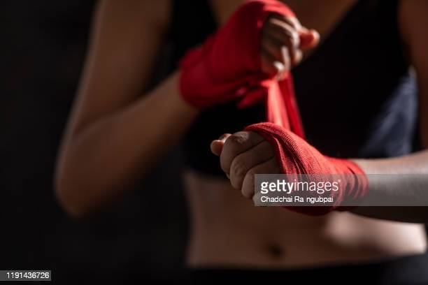boxing bandage. close up of a sportsgirl binding red boxing bandage in a gym. - sports glove stock pictures, royalty-free photos & images