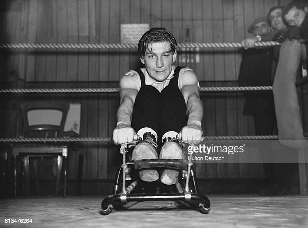 Boxing champion E Boon grits his teeth as he exercises on a rowing machine