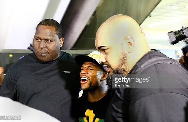 Boxing champion Floyd Mayweather arrives at OR Tambo International Airport with his bodyguards on January 15 2014 in Johannesburg South Africa The...