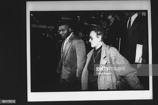 Boxing champion Mike Tyson holding hands w. 86-yr-old foster mother Camille Ewald w. Sparring partner Hurricane Muhammed behind her at press filled...