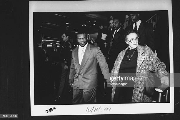 Boxing champion Mike Tyson winking & holding hands w. 86-yr-old foster mother Camille sparring partner Hurricane Muhammed behind her at press filled...